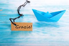 Label with the Italian Word Grazie which means Thanks and a Boat Stock Photos