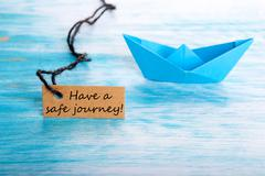 Label with Have a Safe Journey and a Boat in the Background Stock Photos