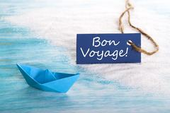 A Blue Label with Bon Voyage which means Safe Trip at the Beach with a Boat - stock photo