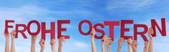 Many Hands Holding the Words Frohe Ostern Means Happy Easter in the Sky - stock photo
