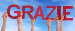 Hands Holding the Italian Word Grazie which means Thanks in the Sky - stock photo
