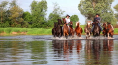 Two cowboys on horses ford the river Stock Footage