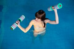 Stock Photo of Pretty girl doing aqua aerobic exercise
