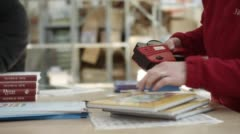 Woman adding Price Tags To Books Stock Footage