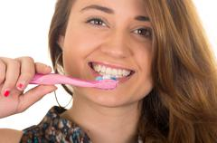 beautiful young smiling woman brushing teeth - stock photo