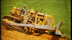 133 - Caterpillar bulldozer moves dirt at job site - vintage film home movie Stock Footage