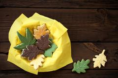 Autumnal Leaf Cookies in a Yellow Bowl on Wood with Copy Space for Your Text - stock photo