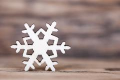 Stock Photo of A Wooden Snowflake on a Wooden Plank, Winter Background