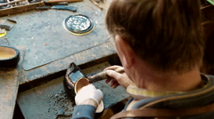 Clog maker is painting a clog black Stock Footage