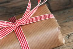 Closeup of a Rustic Present, Gift Wrapped with Red White Ribbon - stock photo