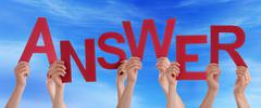 Many Hands Holding the Red Word Answer in the Sky - stock photo