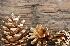 Golden Fir Cones on Wood as Christmas or Winter Background Stock Photos