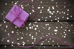 Purple Gift With Ribbon On Wooden Background With Snowflakes - stock photo