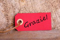 A Red Tag on Wood with the Italian Word Grazie which means Thanks - stock photo
