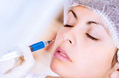 Closeup of woman receiving cosmetic injection through nose Stock Photos