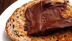 Slow motion spreading of chocolate hazelnut butter on whole wheat toast Stock Footage