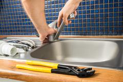 Close-up Of Plumber's Hand Fixing Tap Of Sink - stock photo