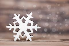 Christmas or Winter Background, Single Snowflake on Wood with Bokeh Backgroun Stock Photos