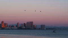 Armed helicopter fly over San Diego skyline - stock footage