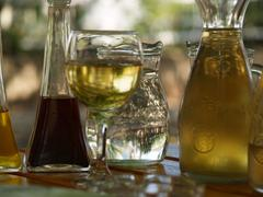 Bowls with wine, water and oil on wooden table Stock Photos