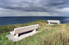 benches on cliff near the sea with stormy clouds - stock photo