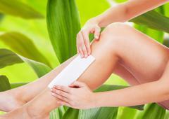 Woman Waxing Her Legs - stock photo
