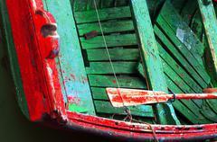 rusty oars in an old wooden boat - stock photo
