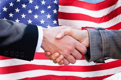 Close-up Of Two Businesspeople Shaking Hands In Front Of American Flag - stock photo