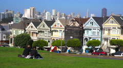 People relax in a park admiring San Francisco's Victorian houses. Stock Footage