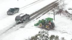 4K tractor plowing snow near busy road in snow storm Stock Footage