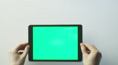 Putting Tablet PC with Green Screen on the White Table and Starting to Use it Stock Footage