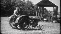 294 - farmer drives his new tractor around the barnyard -vintage film home movie Stock Footage