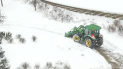 4K John Deere tracktor plowing snow from right to left of screen Stock Footage