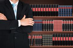 Close-up Of Male Lawyer With Arm Crossed Standing In Front Of Book Shelf Stock Photos