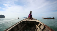 Boy sits on longtail boat sailing out beach in tropics Stock Footage