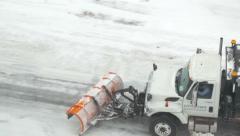 4K overhead shot of city snow plow / sand truck plowing street Stock Footage