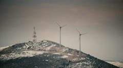 Wind mill turbines blades rotating generating power on mountain long shot Stock Footage
