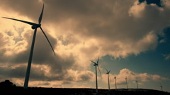 Wind mill turbines blades rotating generating power sunset clouds Stock Footage