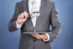 Auditor holding magnifying glass and tablet. Over blue background Stock Photos