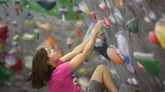 Girl climbs on the training wall during a training session on the climbing gym. Stock Footage