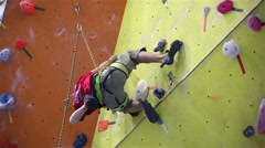 Boy climbs on the training wall during a training session on the climbing gym. Stock Footage