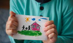 Child holds a drawn house with family Stock Photos