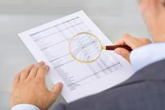 Auditor inspecting document. Over the shoulder view - stock photo