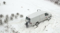 4K frustrated motorist kicking at snow trying to free van Stock Footage