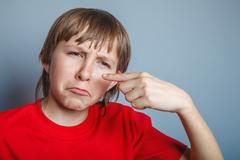 European-looking boy of ten years pimple on the nose, upset over Stock Photos