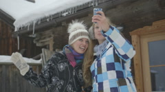 Two young women taking selfie in snow Stock Footage
