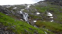 Majestic waterfall streams down green lush mountain Stock Footage