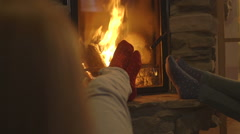 Young women relaxing by fireplace Stock Footage