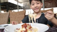 Little asian child eating pasta at restaurant . Stock Footage
