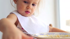 Caucasian little girl independently eats. Small child eats appetizing. Stock Footage